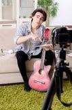 Jeune vid?o de enregistrement de joueur de guitare pour son blog photo libre de droits