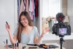 Jeune vidéo femelle asiatique de vlog d'enregistrement de blogger avec l'influencer en ligne de cosmétique de maquillage à la mai images libres de droits