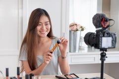 Jeune vidéo femelle asiatique de vlog d'enregistrement de blogger avec l'influencer en ligne de cosmétique de maquillage à la mai photos libres de droits