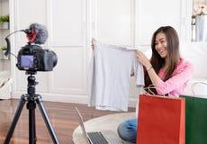 Jeune vidéo femelle asiatique de vlog d'enregistrement de blogger avec l'influencer en ligne de T-shirt de tissus d'examen à la m photo libre de droits