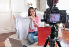 Jeune vidéo femelle asiatique de vlog d'enregistrement de blogger avec l'influencer en ligne de T-shirt de tissus d'examen à la m image libre de droits
