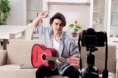 Jeune vid?o de enregistrement de joueur de guitare pour son blog image stock