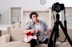 Jeune vid?o de enregistrement de joueur de guitare pour son blog photos stock