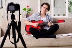 Jeune vid?o de enregistrement de joueur de guitare pour son blog photographie stock libre de droits