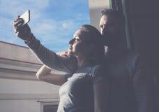 Jeune ville de vacances d'été de couples Femme de photo et homme barbu faisant le téléphone portable de selfie dans le grenier mo Images libres de droits