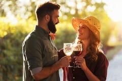 Jeune vin de sourire d'échantillon de couples au vignoble d'établissement vinicole photos stock