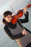 Jeune violoniste en mer Images stock