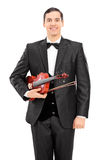 Jeune violoniste tenant un violon et une pose Photos stock