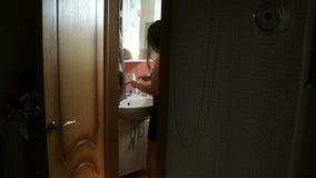 Jeune visage aux cheveux longs de lavage de femme et se brosser les dents dans la salle de bains la fille dans la chemise de nuit banque de vidéos