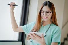 Jeune visage de sourire de femme de docteur avec le stéthoscope regardant le comprimé Co Image libre de droits