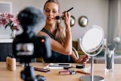 Jeune vlogger femelle enregistrant une émission de maquillage photos stock