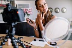 Jeune vlogger femelle enregistrant une vidéo de maquillage pour son vlog image libre de droits