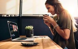 Jeune vlogger femelle observant son vlog sur l'ordinateur images stock
