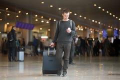 Jeune voyageur à l'aide du téléphone portable dans l'aéroport Image stock