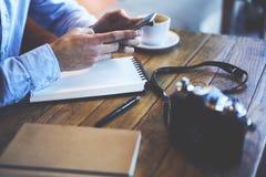 Jeune voyageur de blogger de hippie dans la connexion tout en se reposant à la table en bois dans le café Image stock