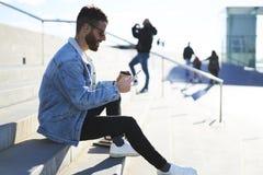 Jeune voyageur de blogger de hippie dans une veste de denim utilisant le smartphone et Internet 4G avec des amis Photos libres de droits