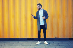Jeune voyageur de blogger de hippie dans une veste de denim utilisant le smartphone et l'Internet 4G modernes Image stock