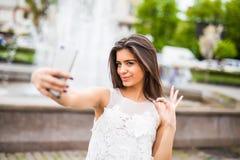Jeune voyageur féminin heureux prenant le selfie sur la rue avec le geste correct Photos libres de droits