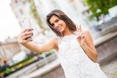 Jeune voyageur féminin heureux prenant le selfie sur la rue avec le signe de victoire Image stock