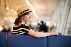 Jeune voyageur féminin s'asseyant dans le salon de attente images libres de droits