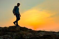Jeune voyageur heureux d'homme trimardant avec le sac ? dos sur Rocky Trail au coucher du soleil chaud d'?t? Concept de voyage et photographie stock libre de droits
