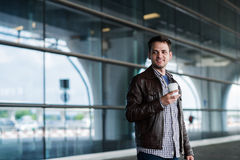 Jeune voyageur masculin beau élégant avec le poil se tenant dehors près du terminal d'aéroport Veste de port d'homme et Photographie stock libre de droits
