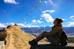 Jeune voyageur s'asseyant à la nuance sur la falaise au-dessus de la montagne des drapeaux colorés de prière dans Leh, Ladakh, In Photo libre de droits