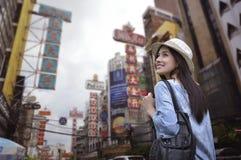 Jeune voyageuse asiatique de femme avec un sac à dos sur son épaule et chapeau de voyage images stock