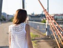 Jeune walkong caucasien heureux de femme sur le vieux pont en parc de ville extérieur Détendez le concept d'été de mode de vie photo stock