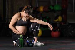 Jeune wate potable de femme enceinte de bouteille en plastique dans le gymnase photo libre de droits