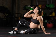 Jeune wate potable de femme enceinte de bouteille en plastique dans le gymnase photos libres de droits