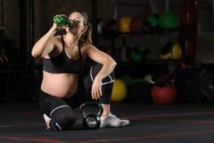 Jeune wate potable de femme enceinte de bouteille en plastique dans le gymnase image libre de droits