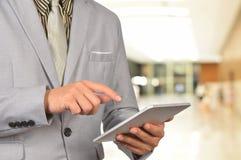 Jeune Web de lecture rapide d'homme d'affaires sur le comprimé à l'aéroport Image stock