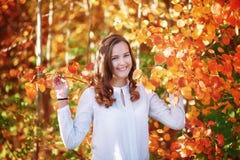 Jeune wooman La jolie fille de sourire dans l'orange lumineuse d'automne part Images stock