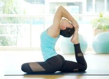 Jeune yoga de pratique de sourire asiatique de femme, se reposant dans un à jambes Photographie stock libre de droits
