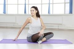 Jeune yoga de sourire de pratiques en matière de femme sur la couverture dans le hall image stock