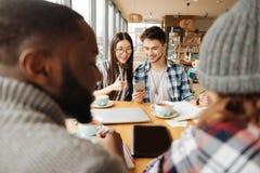 Jeunes à l'aide des smartphones dans le café Photos libres de droits