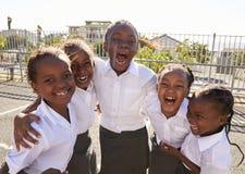 Jeunes écolières africaines dans le terrain de jeu souriant à l'appareil-photo Photographie stock libre de droits