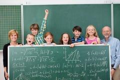 Jeunes écoliers posant avec un tableau Image stock
