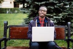 Jeunes étudiant et travail gais africains d'homme sur l'ordinateur portable se reposant sur le banc sur la rue dehors Photos stock