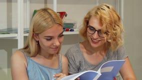 Jeunes étudiantes lisant le manuel à l'amphithéâtre d'université Photo libre de droits
