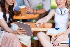 Jeunes étudiants à l'aide du comprimé numérique tout en se reposant ensemble sur le banc dans le parc Images stock