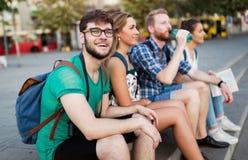 Jeunes étudiants étant heureux aux escaliers de campus images stock