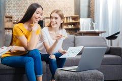 Jeunes étudiants amicaux s'asseyant devant un ordinateur portable et un sourire Photos libres de droits