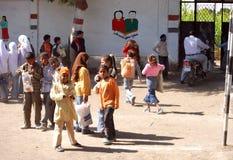 Jeunes étudiants au terrain de jeu à l'école prête à partir Photos stock