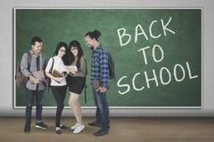Jeunes étudiants avec le texte de nouveau à l'école Image stock