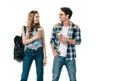 jeunes étudiants de sourire tenant le café pour aller regarder l'un l'autre Photo stock