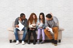 Jeunes étudiants divers se préparant à l'examen à la maison Images stock