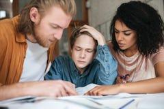 Jeunes étudiants fatigués étudiant dans la salle de classe Deux garçons avec les cheveux blonds et la fille avec travailler boucl Photographie stock