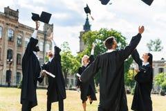 jeunes étudiants gradués jetant des chapeaux d'obtention du diplôme photos stock